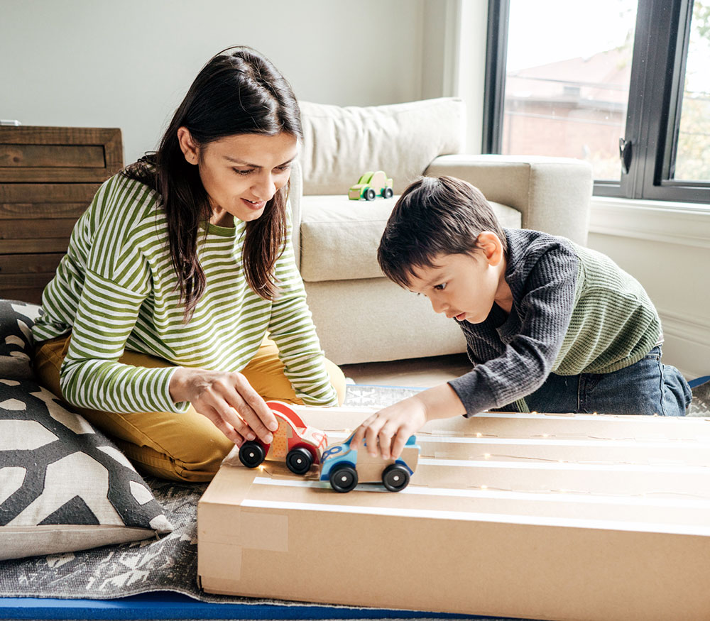 Mother and son playing with wooden trucks